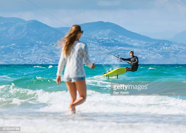 Woman at the beach and kitesurfer.