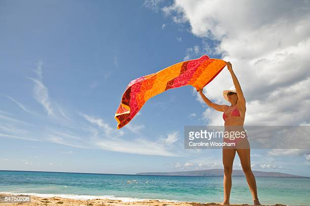 Woman at the beach laying out towel