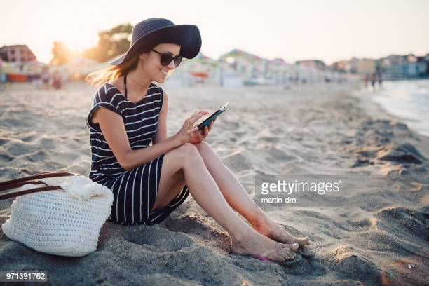 woman at the beach on sunset using smartphone - waimea bay hawaii stock photos and pictures