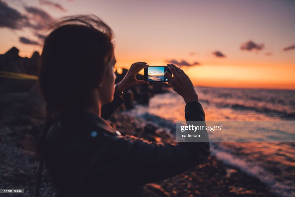Woman at the beach photographing the sunset : Stock Photo