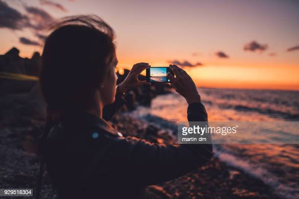 woman at the beach photographing the sunset - photo messaging stock pictures, royalty-free photos & images