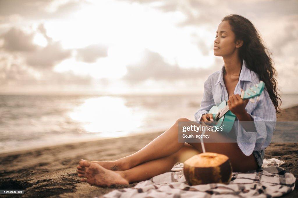 Frau am Strand spielt ukulele : Stock-Foto