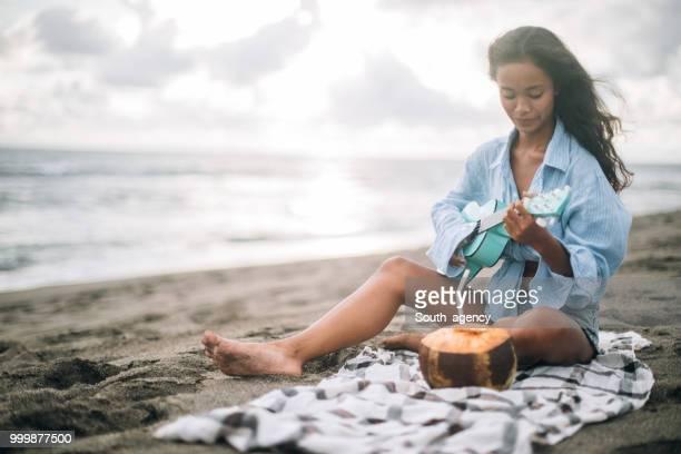 Woman at the beach playing ukulele