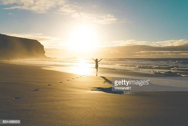 Woman at the beach running to the water at sunset