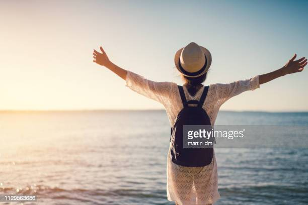 woman at the beach saluting the sun - admiration stock pictures, royalty-free photos & images