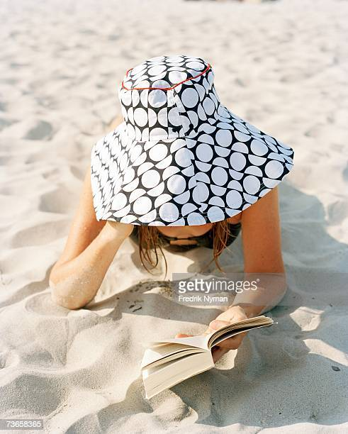 A woman at the beach with a book.