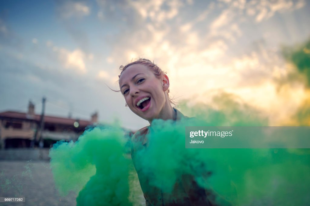 Woman at the beach with smoke bomb : Stock Photo
