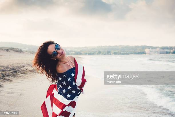Woman at the beach wrapped in american flag
