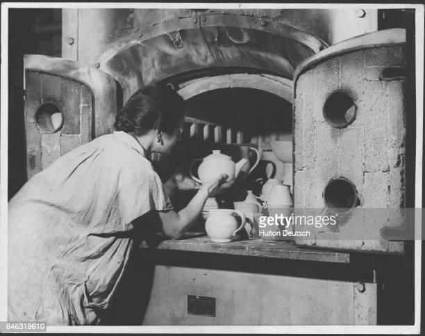 Woman at the Central School for Arts and Crafts in London places teapots, cups and saucers in a kiln for firing.
