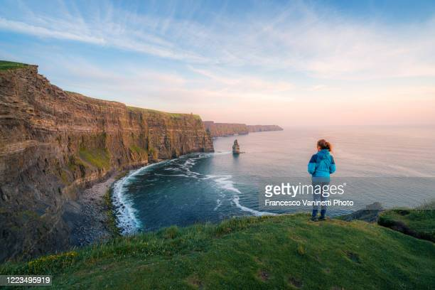 woman at the cliffs of moher, ireland. - ireland stock pictures, royalty-free photos & images