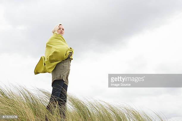 Woman at the coast in blanket