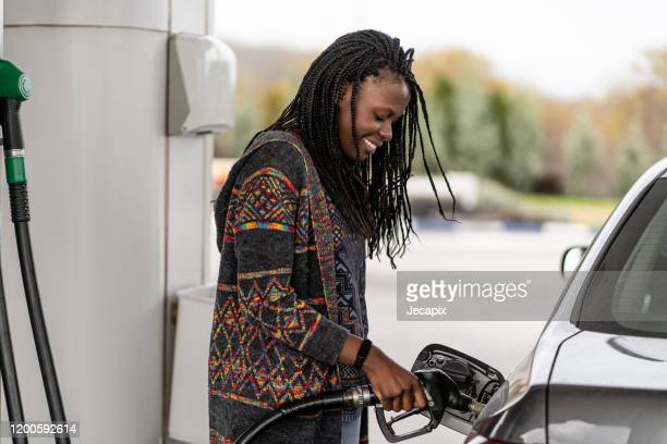 woman at the gas station refueling car - gas station stock pictures, royalty-free photos & images