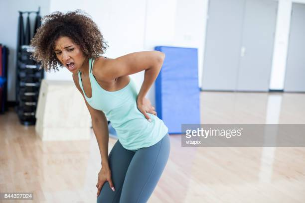 woman at the gym experiencing pain - skinny black woman stock photos and pictures
