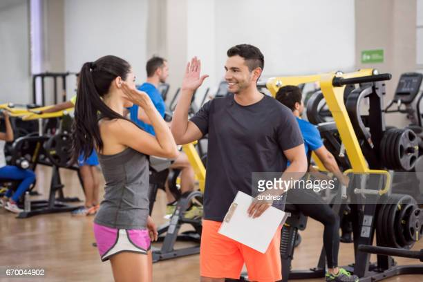 Woman at the gym giving a high-five to her trainer