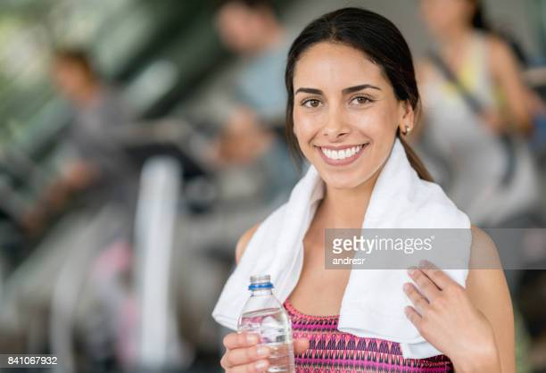 Woman at the gym holding a towel and a water bottle
