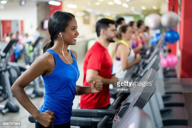 Woman at the gym running on the treadmill and listening to music