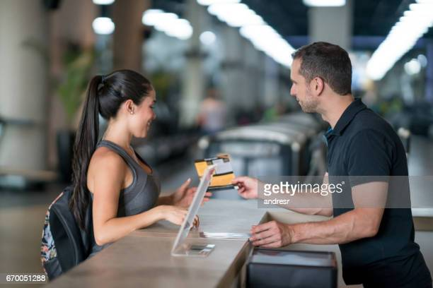 woman at the gym talking to receptionist about membership plans - organized group stock pictures, royalty-free photos & images