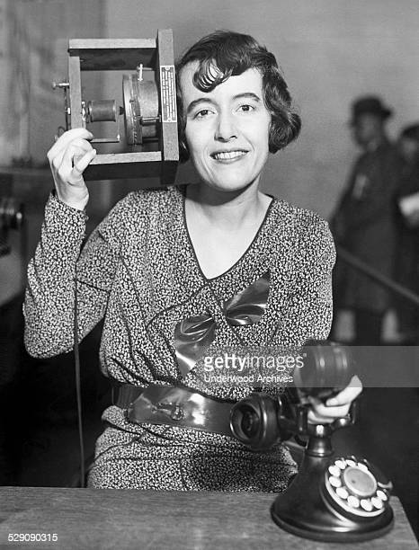 A woman at the Museum of the Peaceful Arts in Manhattan holds a duplicate of Alexander Graham Bell's first 1875 telephone to her ear and holds a...