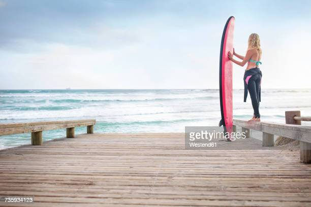 Woman at the ocean with surfboard