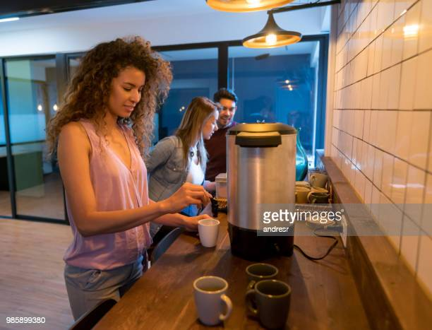カフェテリアでコーヒーを提供するオフィスの女性 - セルフサービス ストックフォトと画像