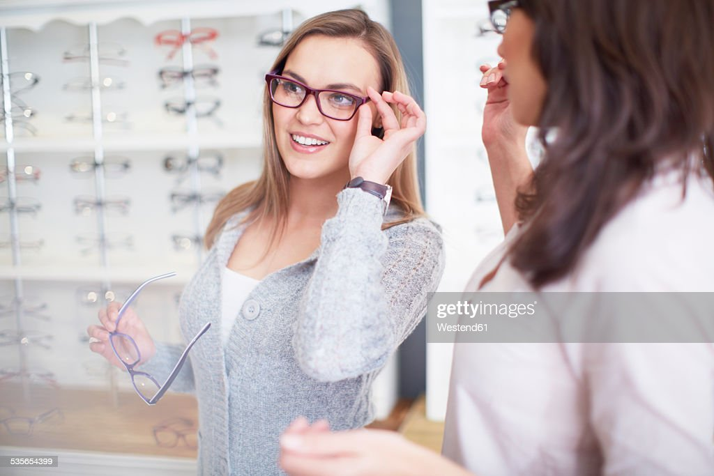Woman at the optician trying on glasses : Stockfoto