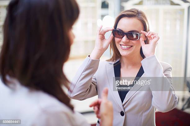 Woman at the optician trying on sunglasses