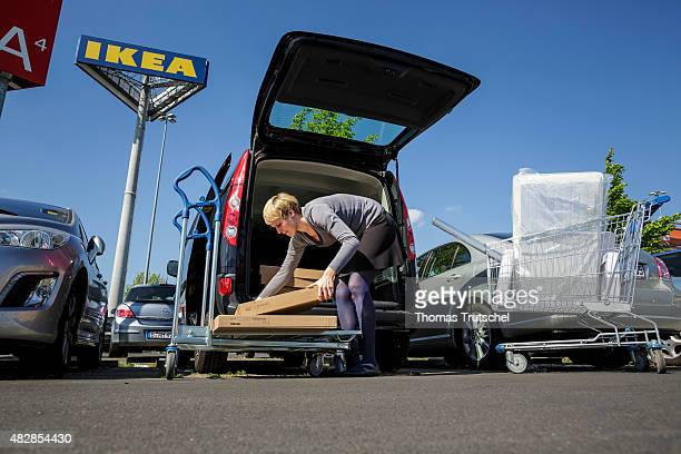 A woman at the parking of IKEA is storring her shopping items in a van IKEA is a furniture store with selfservice