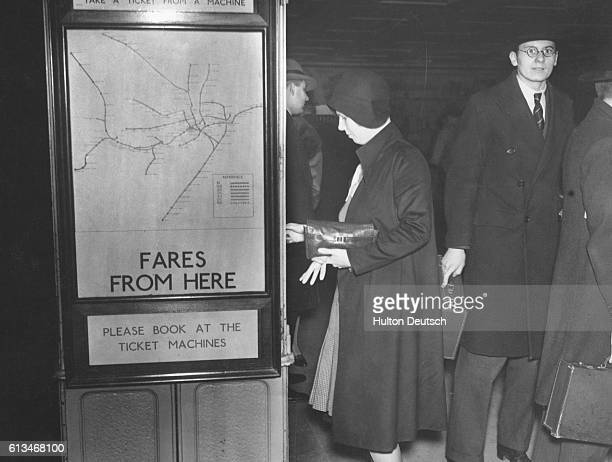 A woman at the Picadilly Circus subway station takes a ticket from the machine