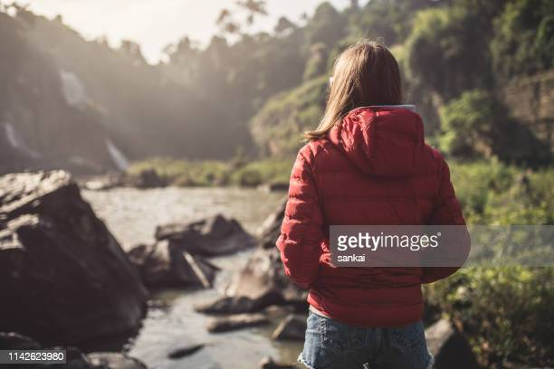 woman at the pongour waterfall in the morning. dalat, vietnam. - behind waterfall stock pictures, royalty-free photos & images