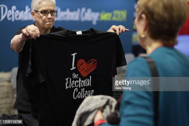 A woman at the Save Our States booth hands out an I Love the Electoral College Tshirt during the annual Conservative Political Action Conference at...