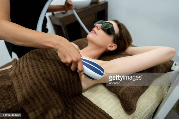 woman at the spa getting a hair removal laser treatment in her armpits - medical laser stock photos and pictures