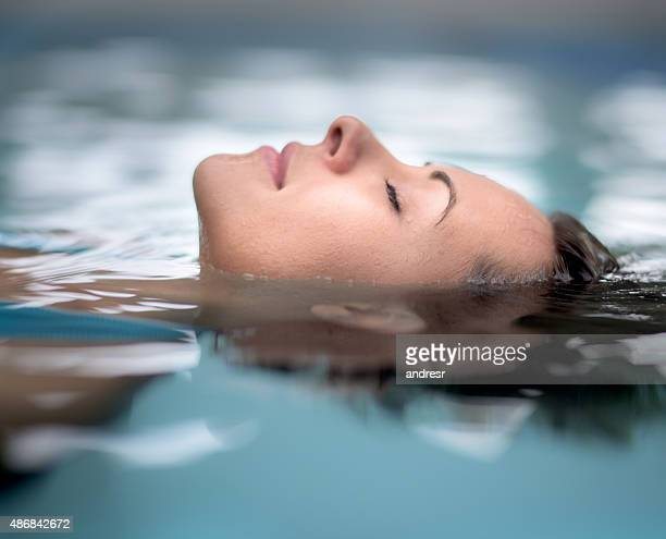 woman at the spa relaxing at the swimming pool - purezza foto e immagini stock