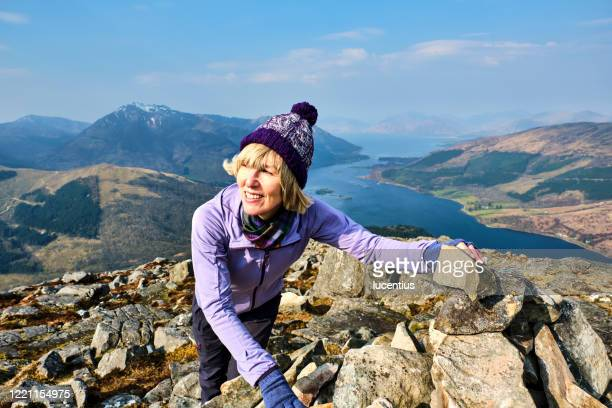 woman at the summit of the pap of glencoe, scotland - mountaineering stock pictures, royalty-free photos & images