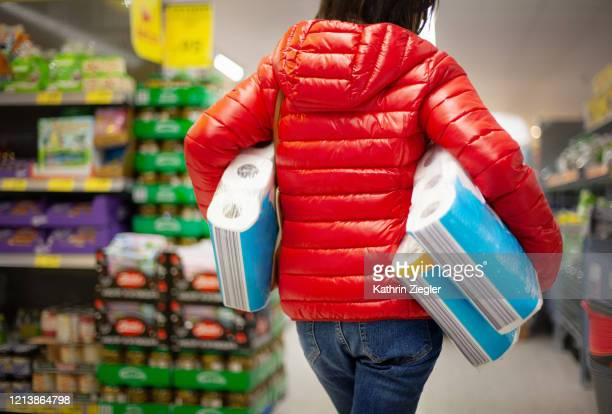 woman at the supermarket, buying paper towels in abundance for lack of toilet paper - panic buying stock pictures, royalty-free photos & images