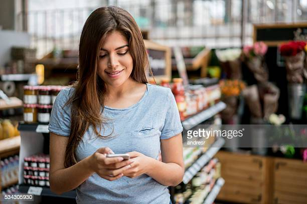 Woman at the supermarket going through a shopping list