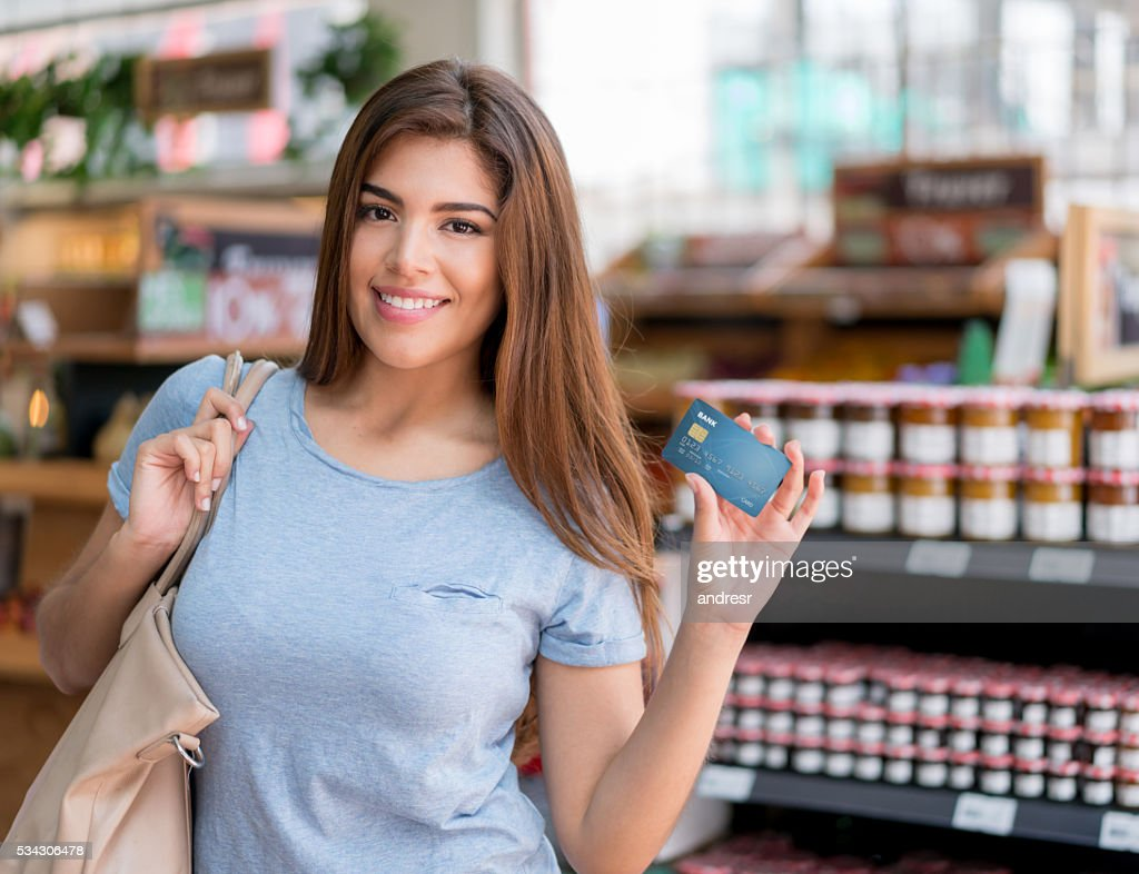 Woman at the supermarket paying by card : Stock Photo