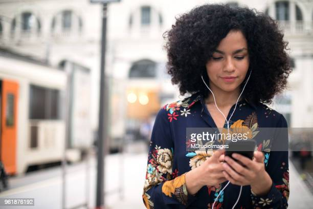 woman at the train station using mobile phone. - listening stock pictures, royalty-free photos & images