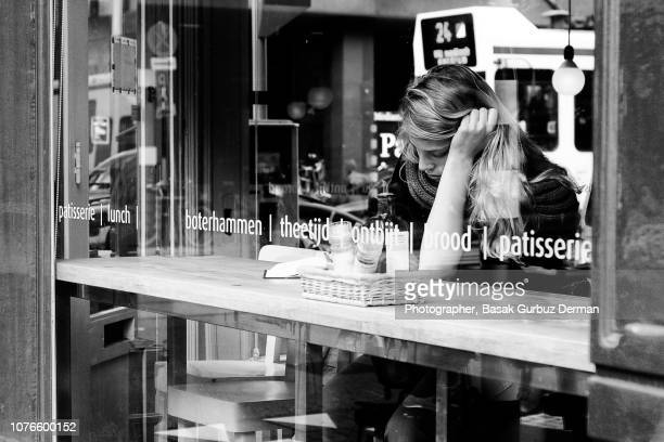 woman at the window of a cafe - basak gurbuz derman stock photos and pictures
