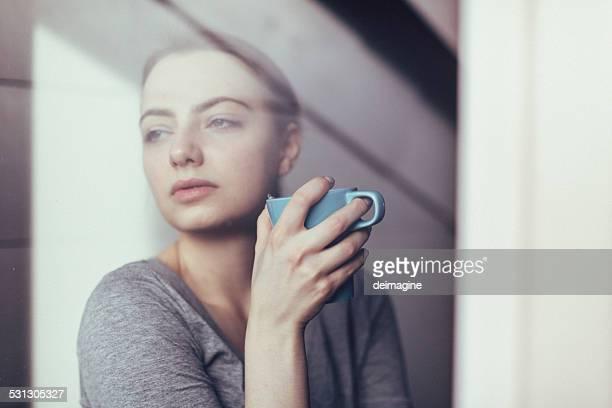 Femme à la fenêtre avec petit déjeuner tasse