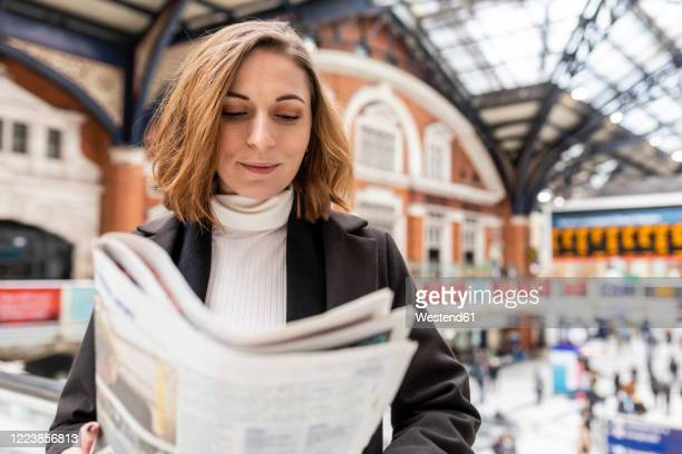 woman at train station reading a newspaper, london, uk - newspaper stock pictures, royalty-free photos & images