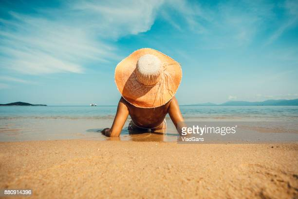 woman at tropical beach - brown hat stock photos and pictures