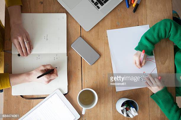 Woman at wooden table writing in notebook with son painting a picture