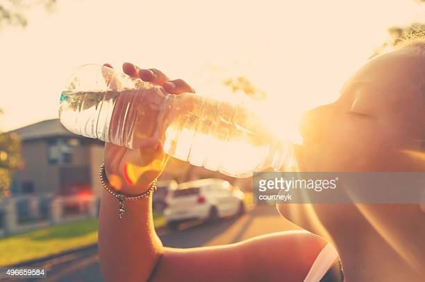 Woman athlete drinking water from a bottle