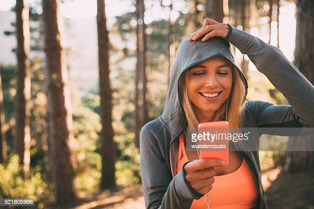 Woman athlete in exercise hoodie taking a selfie in nature