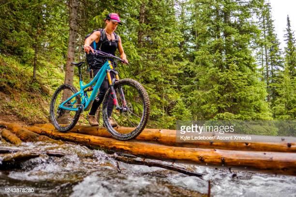 woman athlete pushes mountain bike across slippery log bridge over creek - forward athlete stock pictures, royalty-free photos & images
