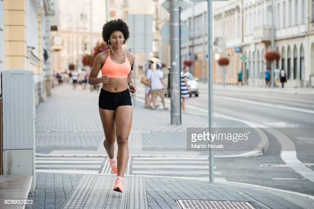 Woman athlete running on city street