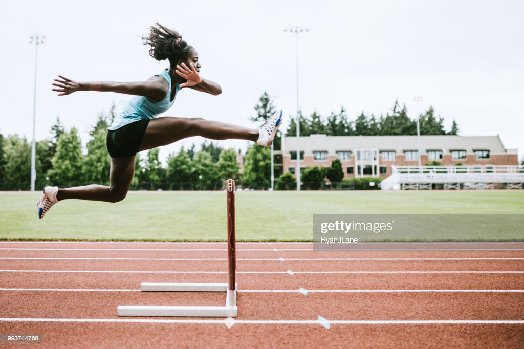 Woman Athlete Runs Hurdles for Track and Field : Stock Photo
