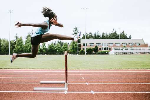 Woman Athlete Runs Hurdles for Track and Field 993744768