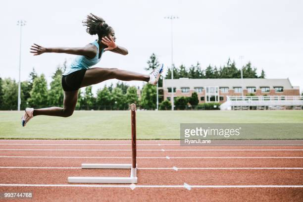 woman athlete runs hurdles for track and field - atleta imagens e fotografias de stock