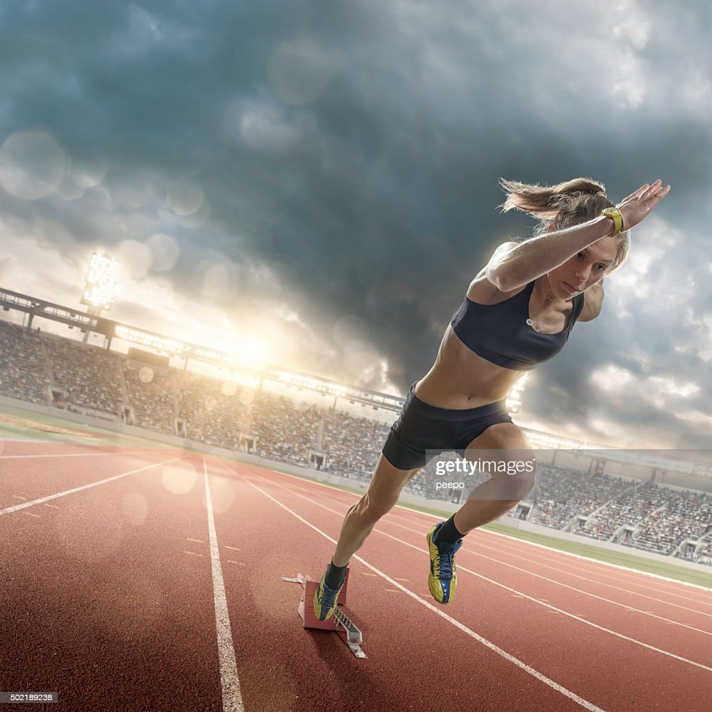 Woman Athlete Sprinting From Blocks on Running Track in Stadium : Stock Photo